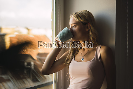 blond young woman drinking coffee from