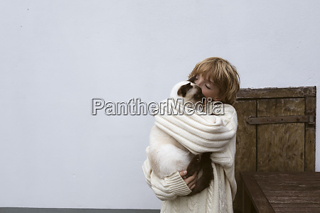 boy holding cat on his arms