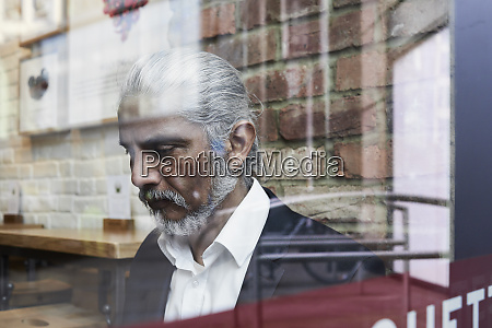 senior businessman behind windowpane in a