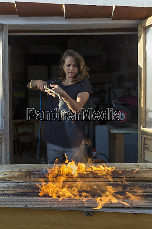 craftswoman burning wood in her workshop