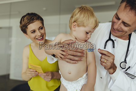 doctor putting band aid on toddlers