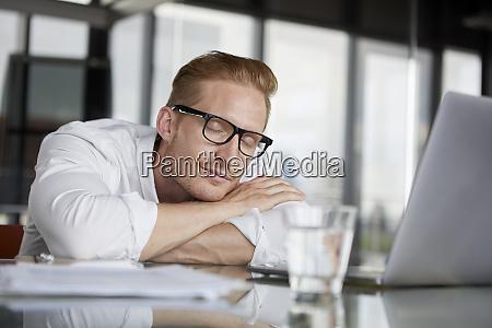 businessman leaning on desk in office