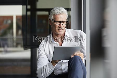 serene businessman sitting on ground in