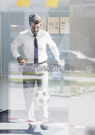 businessman playing football in office