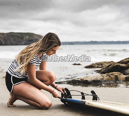 young woman at the beach preparing