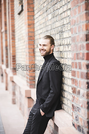 smiling fashionable young man leaning against