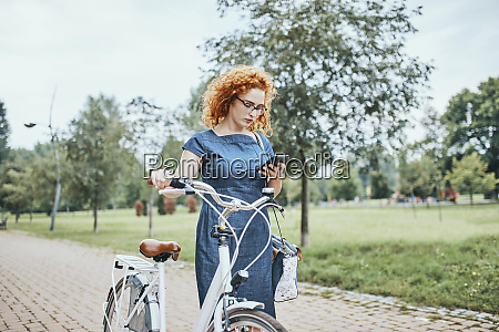 young woman walking in park pushing