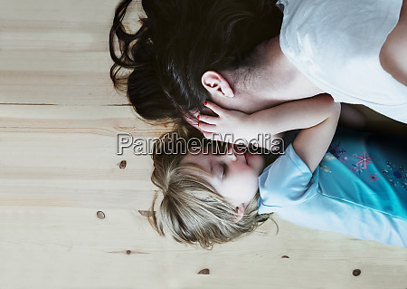 daughter caressing mother lying on floor