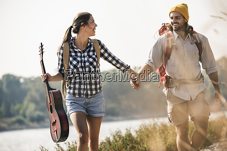 happy young couple with backpacks and