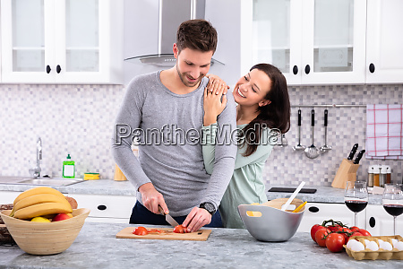 smiling couple preparing food in kitchen