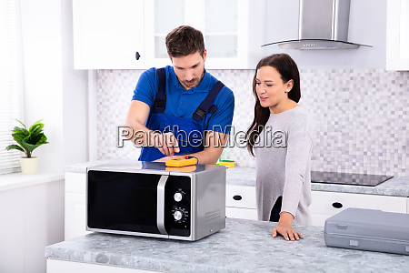 male repairman repairing oven in kitchen