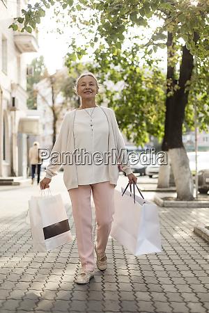 smiling senior woman walking on pavement