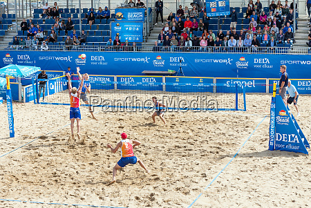 young men playing professional beach volleyball