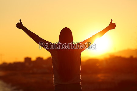 backlight of a woman raising arms