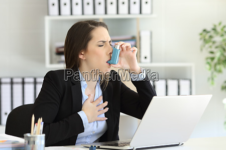 asmathic executive inhaling with an asthma