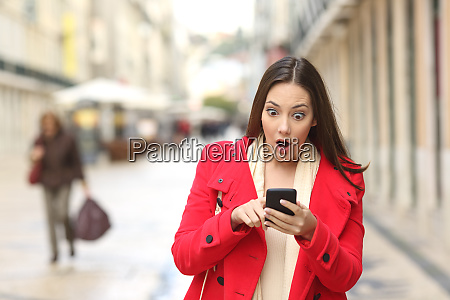 amazed woman checking smart phone in