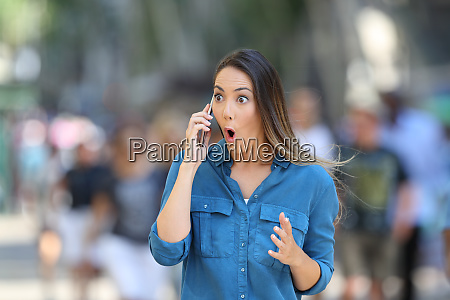 amazed woman receiving news on phone