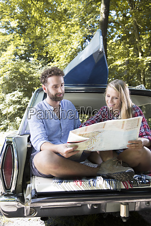 smiling young couple with map and