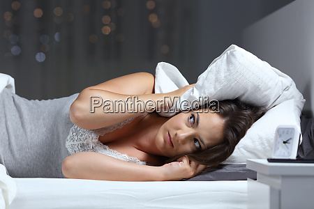 desperate woman trying to sleep hearing