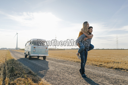 young man carrying girlfriend piggyback on