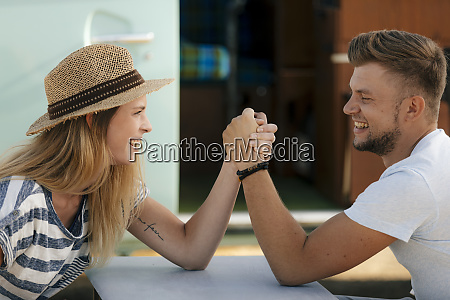 happy young couple armwrestling at camper