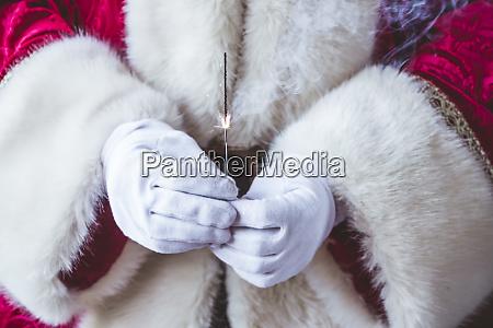 hands of santa claus holding burning