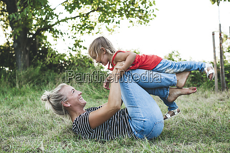 happy mother playing with daughter on