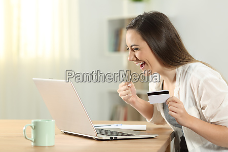 excited woman paying online at home