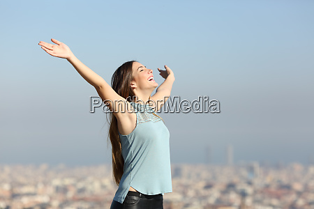 excited woman raising arms celebrating vacation