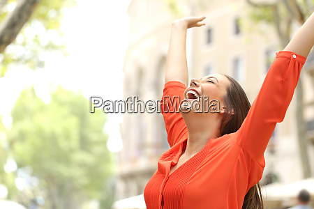 excited woman raising arms in the