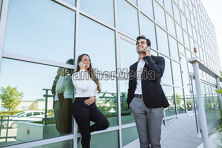 smiling businesswoman and businessman on cell