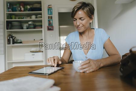 woman sitting at table at home