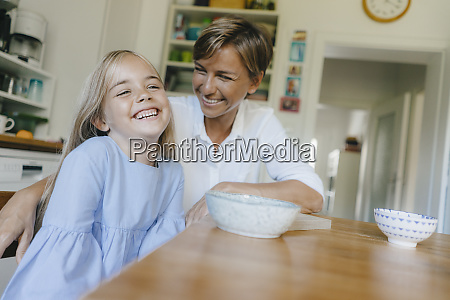 happy mother and daughter sitting at