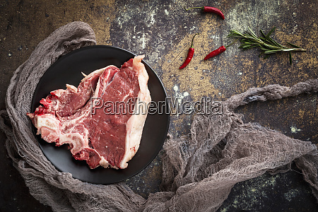 raw beef steak with rosemary and