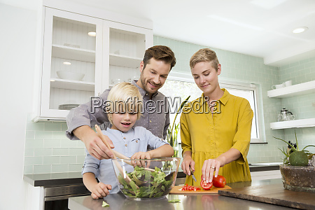 smiling family preparing salad in kitchen