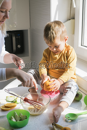 little boy sitting barefoot on worktop