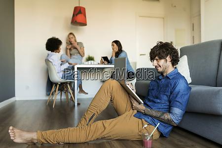 smiling man sitting on floor using