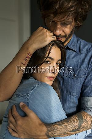tattooed man embracing girlfriend