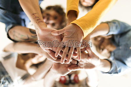 group of happy friends huddling and