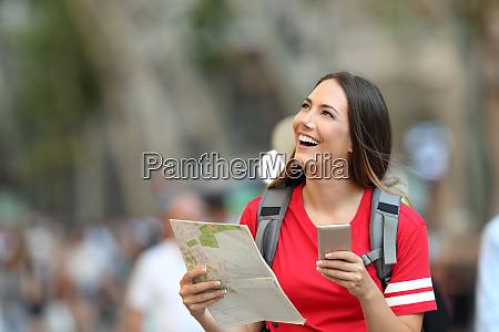 teen tourist holding guide and phone