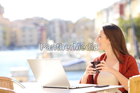 woman with a laptop looking away