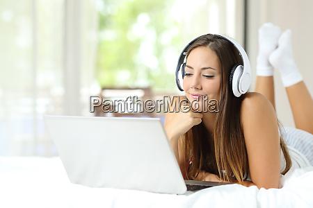 girl watching media on laptop wearing
