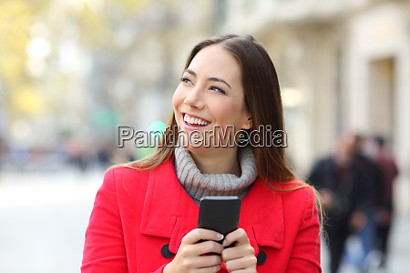 happy woman holding phone looking at