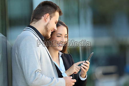 two executives using a mobile phone