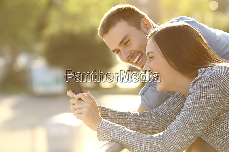 couple laughing with media content in