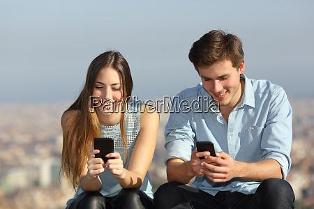 happy couple using their smart phones