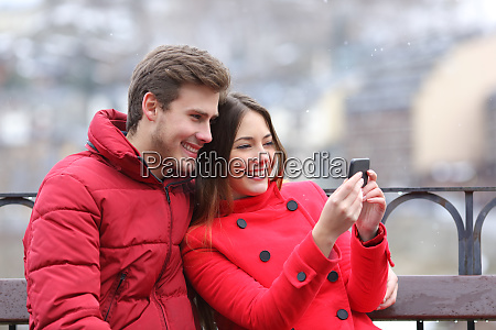 happy couple checking phone on winter