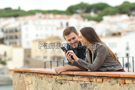 happy couple checking smart phone in