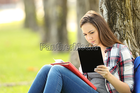 student studying comparing notes on line