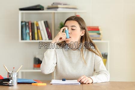 student using an asthma inhaler at